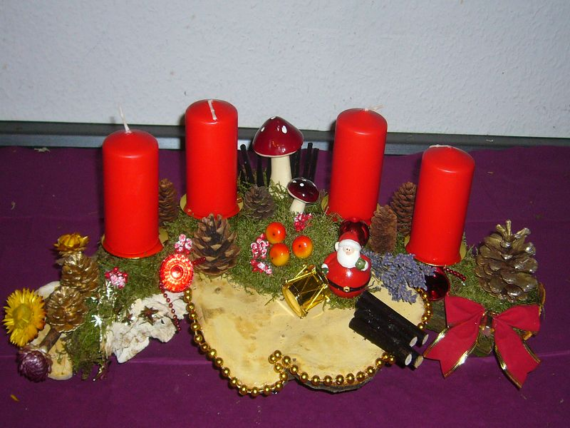 Etwa 50 cm langes und 30 cm tiefes 4er Gesteck mit roten Kerzen, Natur- und künstlicher Dekoration und großem Rotrandigem Baumschwamm für 25,00 €.