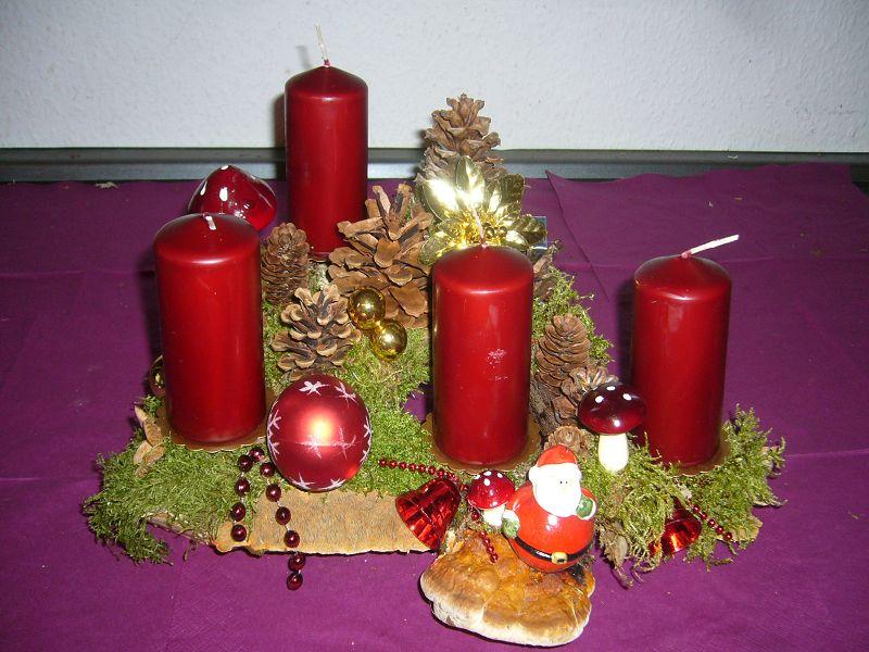 Mittelgroßes 4er Gesteck (ca. 30 cm im Durchmesser) mit weinroten Kerzen und Rotrandigem Baumschwamm für 15,00 €.