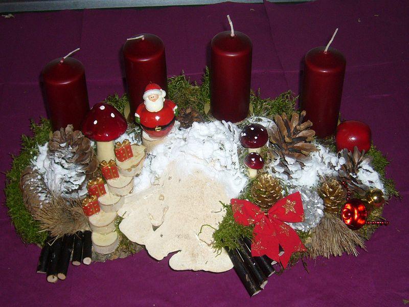 Kompakters 4er Gesteck mit dunkelroten Kerzen, Buckel - Tramete, Weihnachtsdekoration und Schnee für 20,00 €.