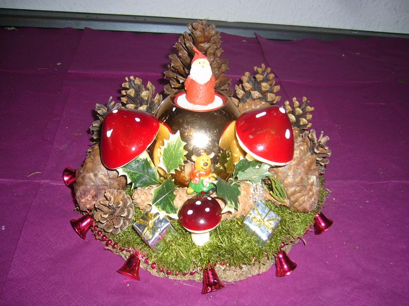 Rundes, kleiners 4er Gesteck auf Baumscheibe, ca. 20 cm im Durchmesser, reichlich Dekoration mit Weihnachtsmann - Teelicht für 12,50 €.