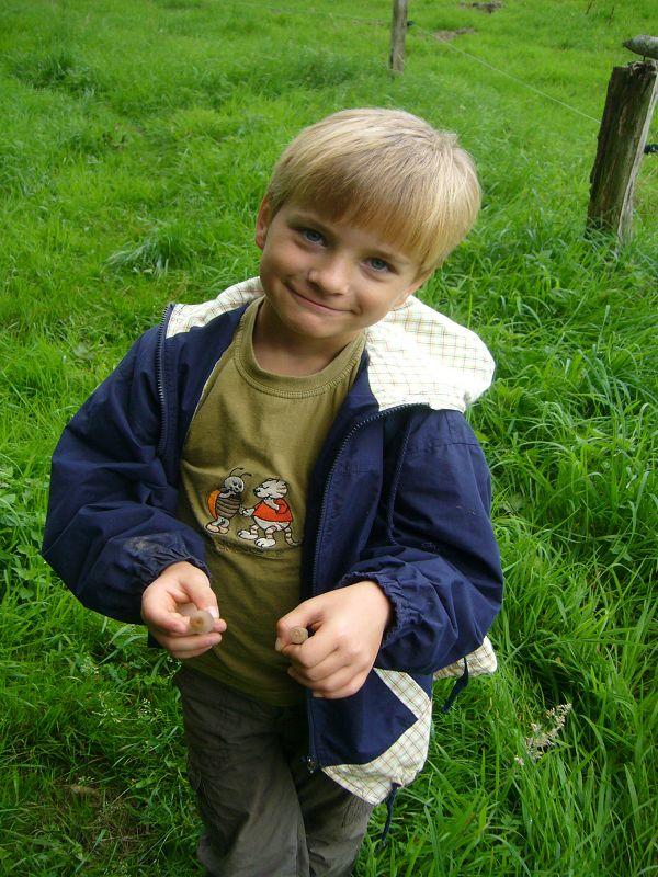 Jonas freut sich und hat zwei kleine, zarte Pilzchen gefunden. Papa wird sie bestimmt kennen!.