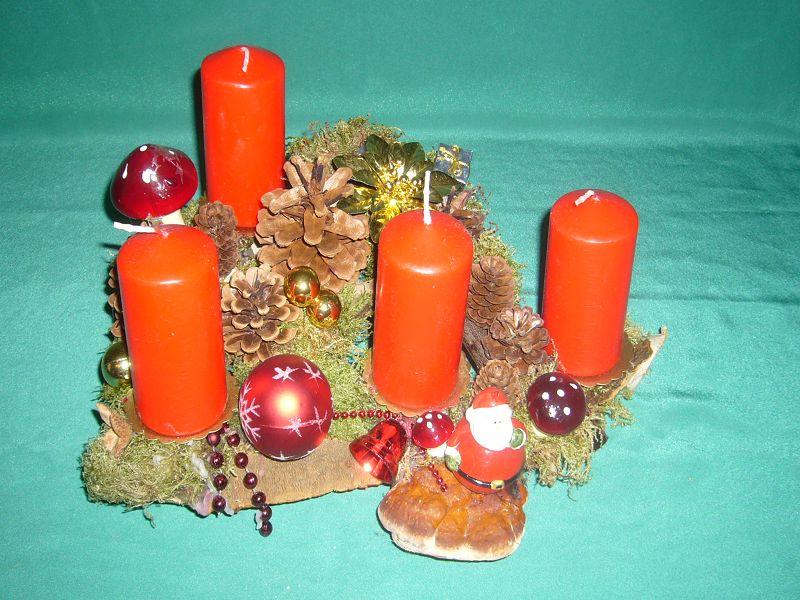Etwa 35 cm langes und teifes 4er Gesteck mit roten Stumpenkerzen auf Astmaterial mit Moos, Rotrandigem Baumschwamm und weitere Dekoration zu 15.00 €.