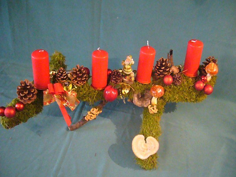 Etwa 70 cm langes und 40 cm tiefes 4er Gesteck mit roten Stumpenkerzen auf einer Stgabel mit Moos und Weinhnachtsdekoration zu 20,00 €.