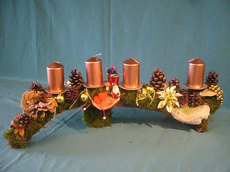 Gut 60,00 cm langes und 15 cm tiefes 4er Gesteck mit goldenen Stumpenkerzen auf einem Ast mit verschiedenen Porlingen und Weihnachtsdekoration zu 15,00 €.