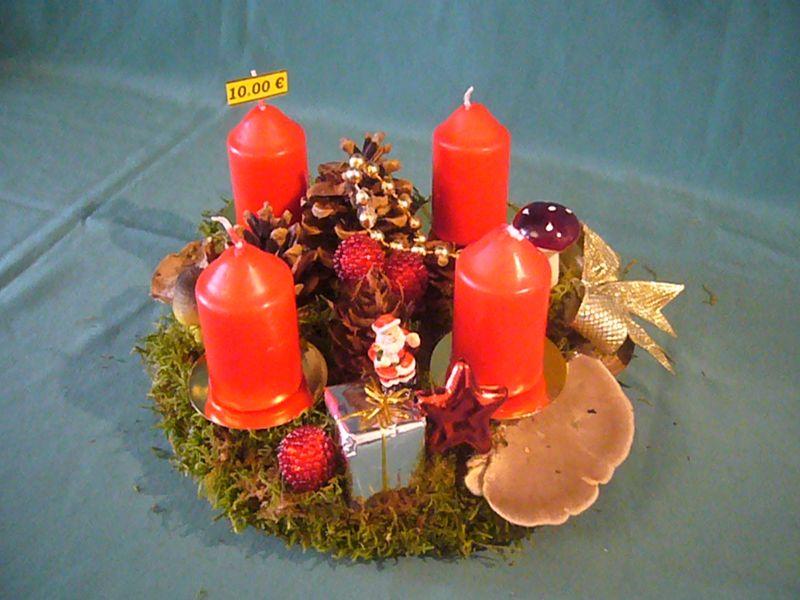 Rundes 4er Gesteck auf Baumscheibe mit natürlicher und künstlicher Dekoration und roten Stumpenkerzen zu 10,00 €.