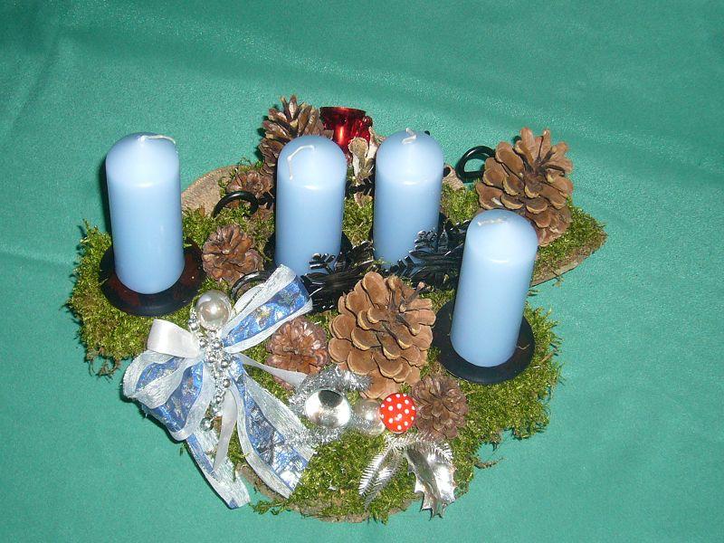 Etwa 30 cm langes und 25 cm tiefes 4er Gesteck mit hellblauen Stumpenkerzen auf Baumscheibe, Kiefernzapfen und Dekoration zu 12,50 €.