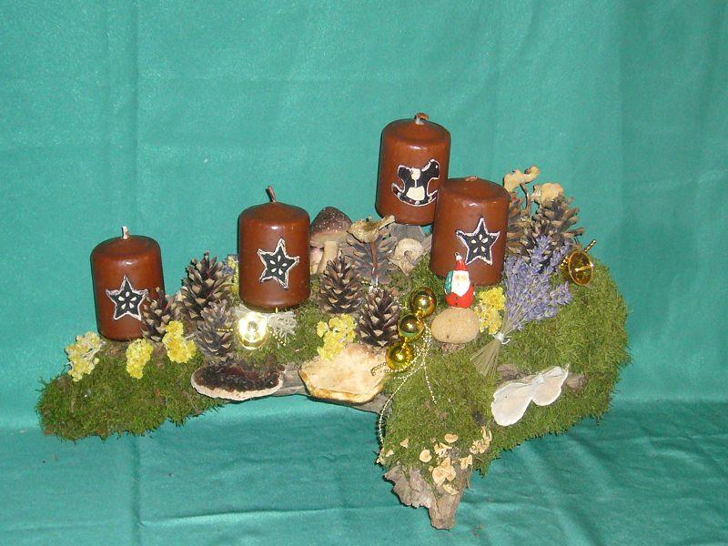 Wuchtiges, etwa 50,00 cm langes, 30,00 cm hohes und tiefes, aber leichtes 4er Gesteck auf Holz mit Moos, Pilzen, Weihnachtsdekoration und weinbraunen Motivkerzen zu 25,00 €.