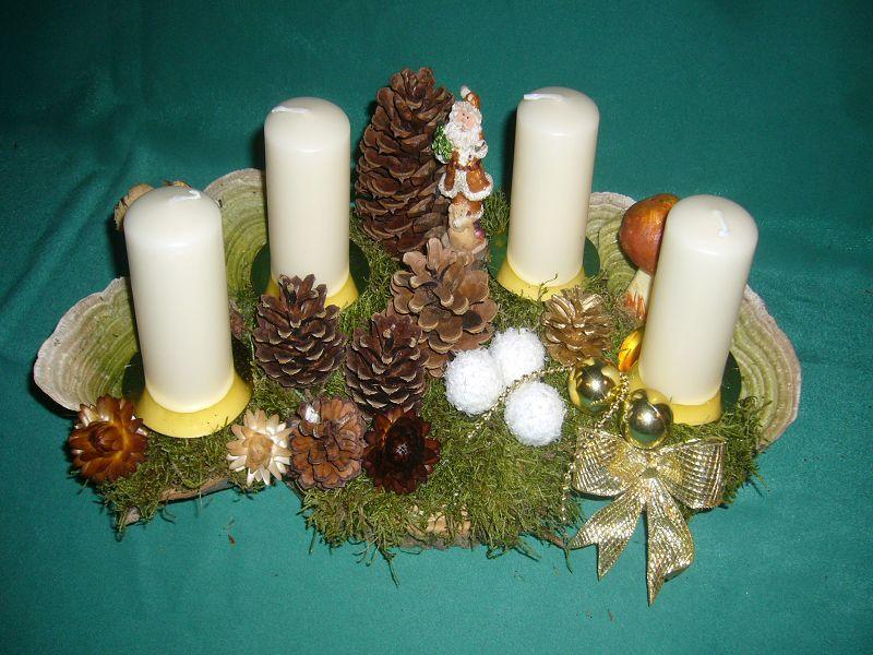Gut 40 cm langes und 20 cm tiefes 4er Gesteck mit weißen Stumpenkerzen, Moos, Zapfen und Weihnachtsfekoration zu 15,00 €.