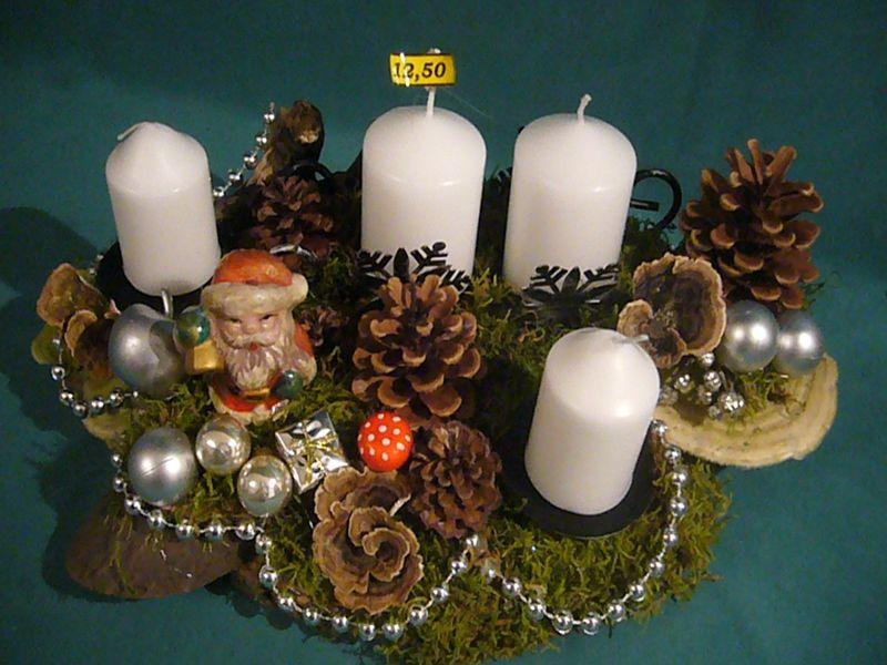 Ovales 4er Gesteck mit weißen Stumpenkerzen auf Baumscheibe mit natürlicher und künstlicher Weihnachtsdekoration. Ca. 35 cm Länge und 25 cm Tiefe zu 12,50 €.