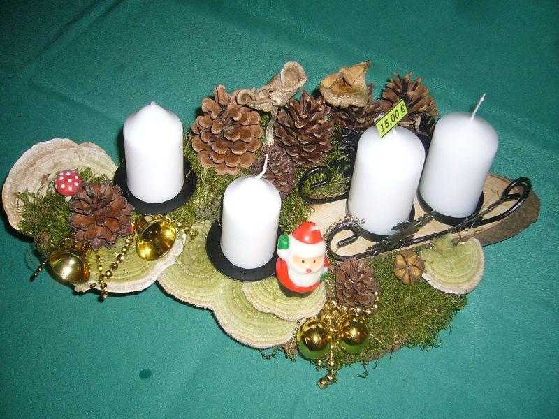 Etwa 40 cm langes und 20 cm tiefes 4er Gesteck mit schneeweißen Stumpenkerzen auf Baumscheibe mit Striegeligen Trameten, Kiefernzapfen und Weihnachtsdekoration zu 15,00 €.