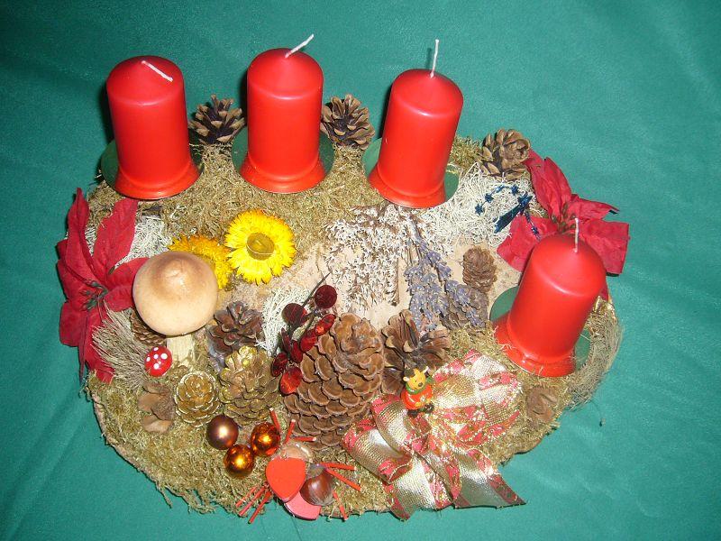Etwa 45 cm langes und 25 cm tiefes 4er Gestecke mit roten Stumpenkerzen auf Rotrandigem Baumschwamm mit Moos, Flechten, Strohblumen, Zapfen mit Pilz- und Weinhachtsdekoration zu 20,00 €.