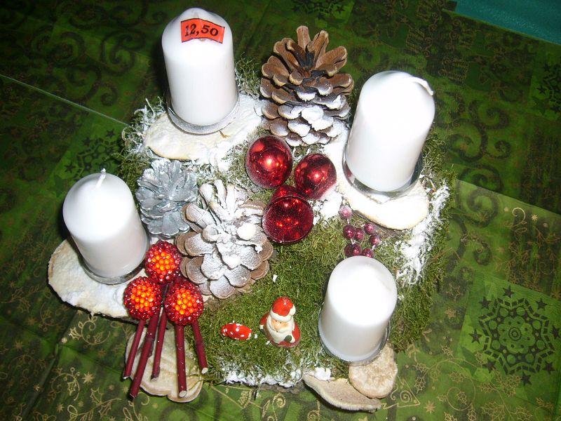 Rundliches 4er Gesteck mit weißen Kerzen, Schnee, Kiefernzapfen und Weihnachtsdekoration, ca. 25 cm in Durchmesser für 12,50 €.