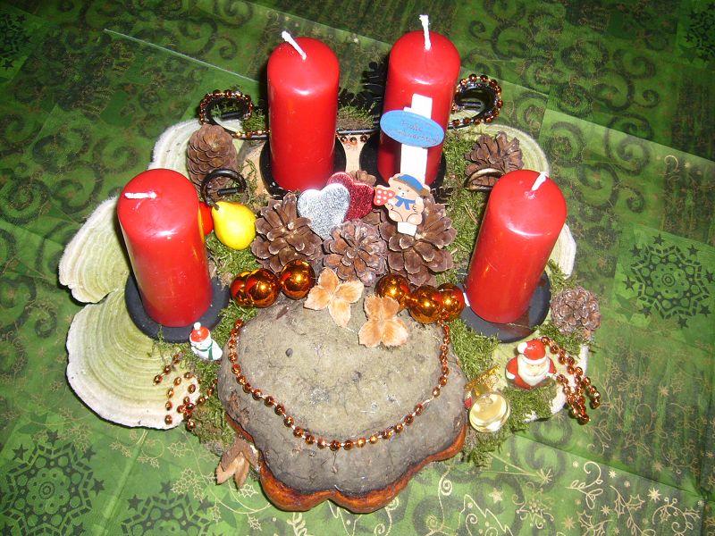 Etwa 35 cm langes und 25 cm tiefes 4er Gesteck mit roten Stumpenkerzen auf Holzscheiben mit Rotrandigem Baumschwamm, Striegeligen Trameten und Weihnachtsdekoration zu 15,00 €.