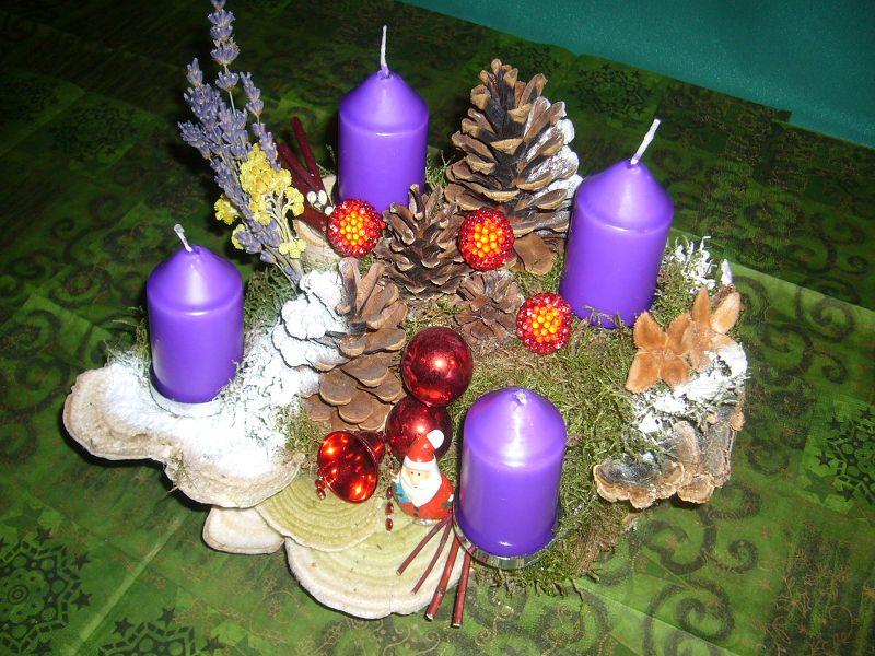 Etwa 30 cm langes und 20 cm tiefes 4er Gesteck mit violetten Stumpenkerzen auf Holzscheibe mit Striegeligen- und Schmetterlingstrameten, Zapfen und Weihnachtsdekoration zu 12,50 €.