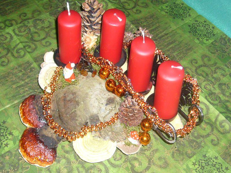 Etwa 30 cm langes und 20 cm tiefes 4er Gesteck mit roten Stumpenkerzen, Rotrandigem Baumschwamm und Striegeligen Trameten sowie Weihnachtsdekoration zu 12,50 €.