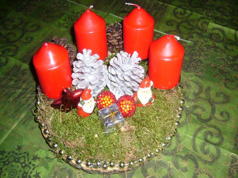 Rundes 4er Gesteck mit roten Stumpenkerzen auf Holzscheibe mit Moos und Weihmachstdekoration, etwa 20 cm im Durchmesser zu 8,00 €.