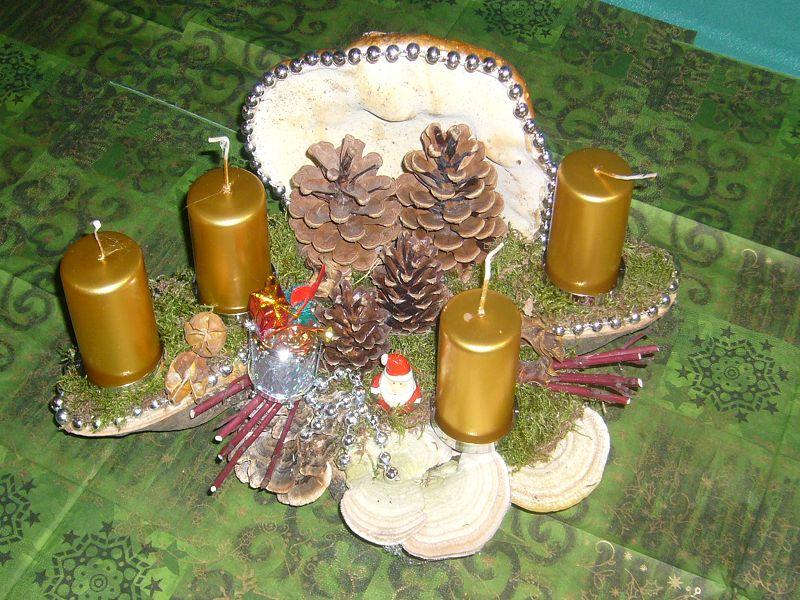 Etwa 35 cm langes und 25 cm tiefes 4er Gesteck mit goldenen Stumpenkerzen, Rotrandigem Baumschwamm und Striegeligen Trameten, Kiefernzapfen und Weihnachtsdekoration zu 12,50 €.