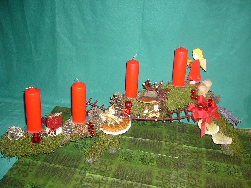 Gut 1 m langes Astgesteck mit 4 roten Stumpenkerzen, Moos, Hartriegeltreppe und Weihnachtsdekoration zu 25,00 €.