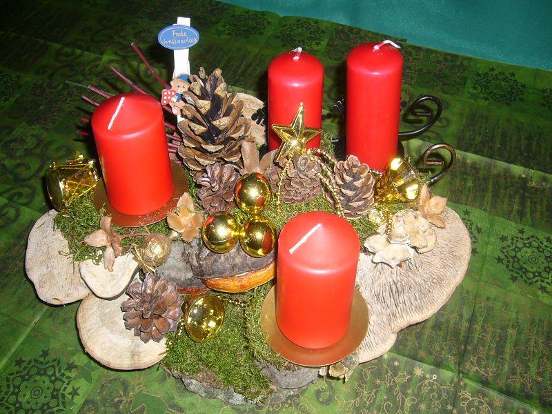 Natürlich gehaltenes 4er Gesteck mit roten Stumpenkerzen, etwa 30 cm im Durchmesser mit Eichen - Wirrlingen und Weihnachtsdekoration zu 12,50 €.