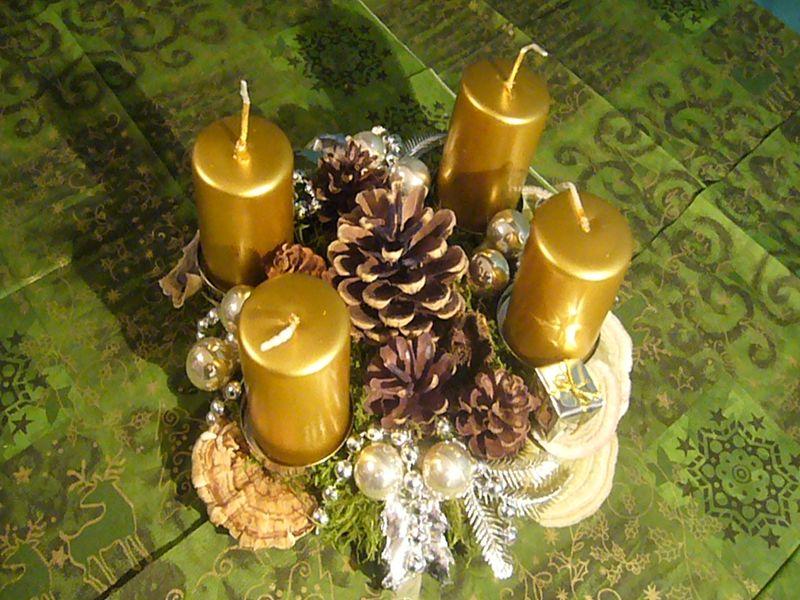 Rundes 4er Gesteck mit 4 goldenen Stumpenkerzen, Kiefernzapfen uns silberner Weihnachtsdekoration zu 8,00 €.