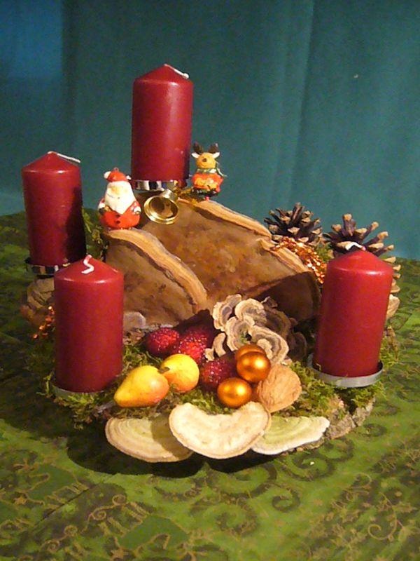 Etwa 30 cm langes, breites und mit Kerzen hohes 4er Gesteck mit weinroten Stumpenkerzen, Echtem Zunderschwamm, Striegeliger- und Schmetterlingstrameten sowie weihnachtlicher Dekoration zu 12,50 €.