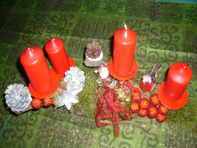 Etwa 40 cm langes und 15 cm tiefes Astgesteck, augebessert aus dem letzten Jahr, mit roten Stumpenkerzen, Moos und Weihnachtsdekoration zu 5,00 €.