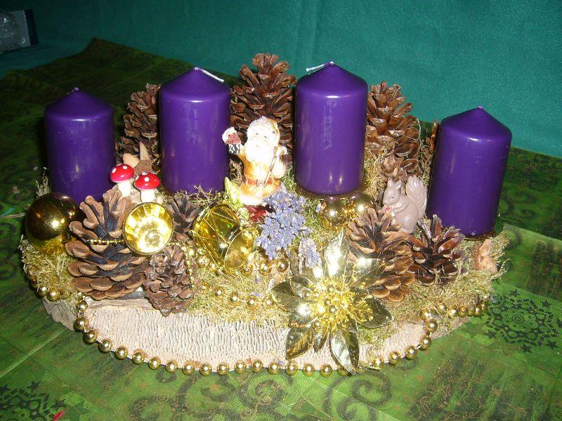Etwa 40 cm langes und 25 cm tiefes 4er Gesteck auf Eichen - Wirrling mit violetten Stumpenkerzen, Moos, Zapfen und Weihnachtsdekoration zu 15.00 €.