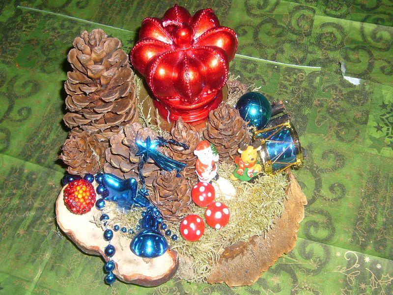 Rundliches 1er Gesteck mit roter Kronenkerze auf Holzscheibe mit Kiefernzapfen und weihnachtlicher Dekoration, ca. 20 cm im Durchmesser zu 6,00 €.
