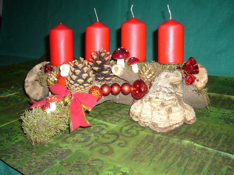 Etwa 35 cm langes und 20 cm tiefes 4er Gesteck auf Astgabel mit roten Stumpenkerzen, echtem Zunderschwamm, Zapfen und weihnachtlicher Dekoration zu 10,00 €.
