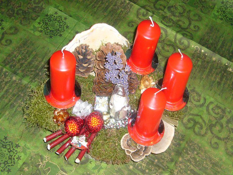Rundliches 4er Gesteck, ca. 30 cm im Durchmesser mit roten Stumpenkerzen, verschiedenen Porlingen, Moos, Zapfen und Weihnachtsdekoration zu 12,50 €.
