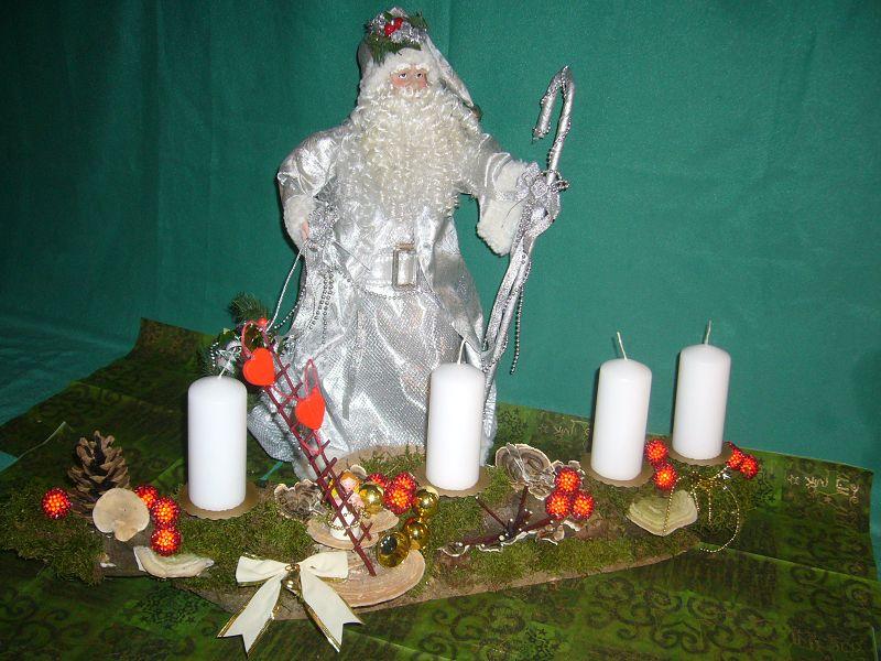 Etwa 80 cm langes und 25 cm tiefes 4er Gesteck mit schneeweißen Stumpenkerzen auf Ast mit Moos, Zapfen und weihnachtlicher Dekoration zu 20,00 €.
