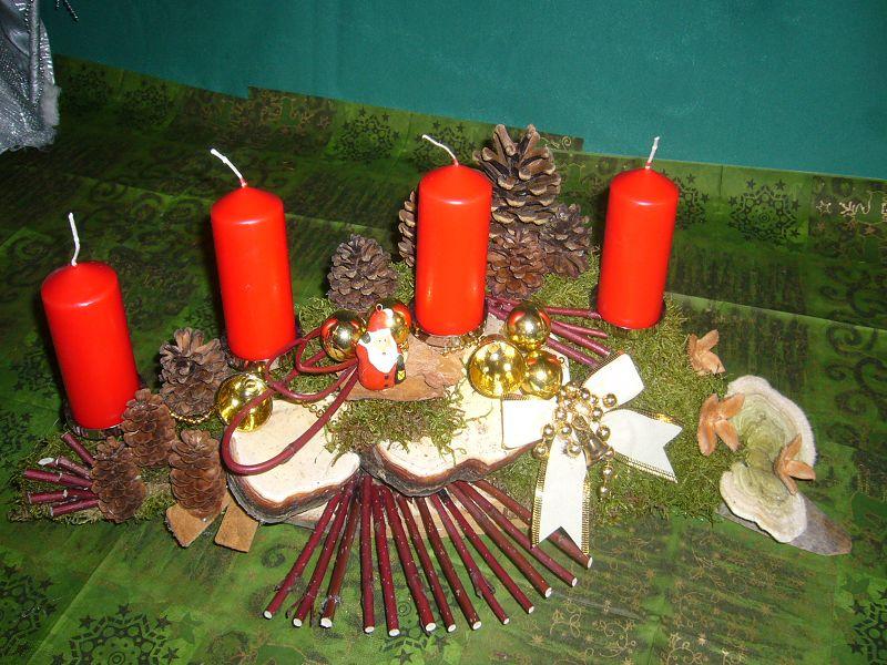 Etwa 40 cm langes und 30 cm tiefes 4er Gesteck mit roten Stumpenkerzen, Moos, Zapfen, Rotrandigem Baumschwamm und Hartriegelfächer zu 15,00 €.