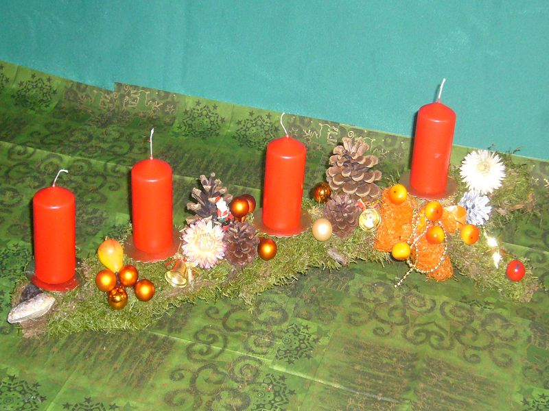 Etwa 50 cm langes und recht schmales Astgesteck mit Moos, Zapfen, weihnachtlicher Dekoration mit 4 roten Stumpenkerzen zu 8,00 €.