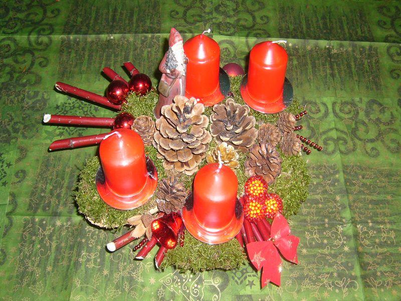 4er Gesteck, etwa 30 cm im Durchmesser, mit roten Stumpenkerzen, Moos, Kiefernzapfen, Hartriegel und Weihnachtsdekoration zu 10,00 €.