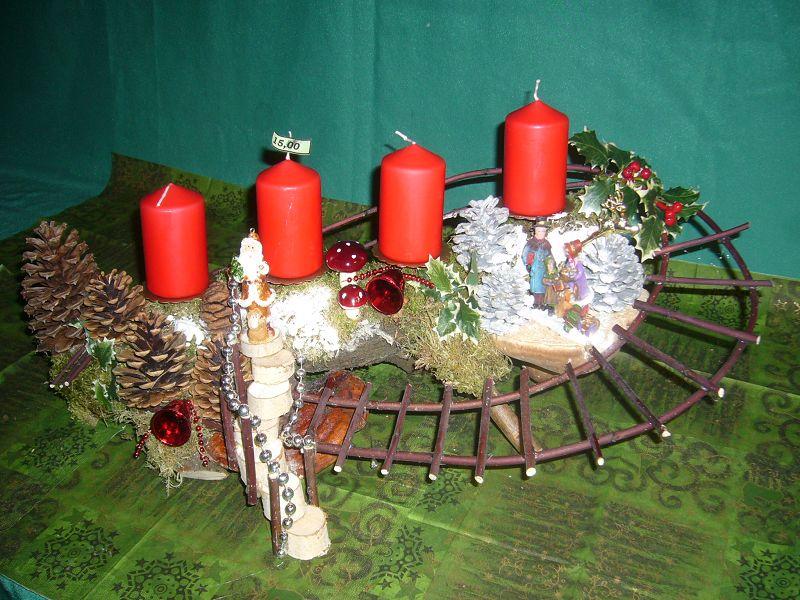 Etwa 70 cm langes und30 cm tiefes 4er Gesteck mit roten Stumpenkerzen auf Ast mit Hartriegeltreppe, Weihnachtsmann auf Birkenporling und ein weterer auf Birkentreppe und Kiefernzapfen für 15,00 €.