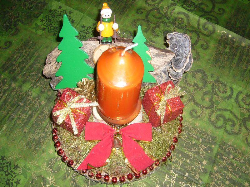 Rundes 1er Gesteck auf Baumscheibe mit Moos, Tannenbäumen, Weihnachtsdekoration und oranger Kerze zu 5,00 €.