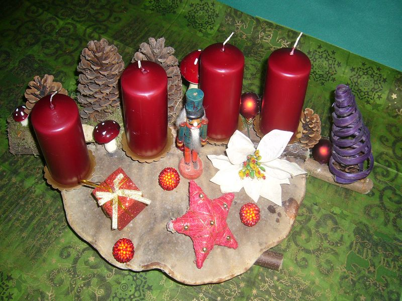Etwa 45 cm langes und 30 cm tiefes 4er Gesteck dunkelweinroten Kerzen auf Rotrandigem Baumschwamm mit Kiefernzapfen, Weihnachtsdekoration und Nußknacker zu 10,00 €.