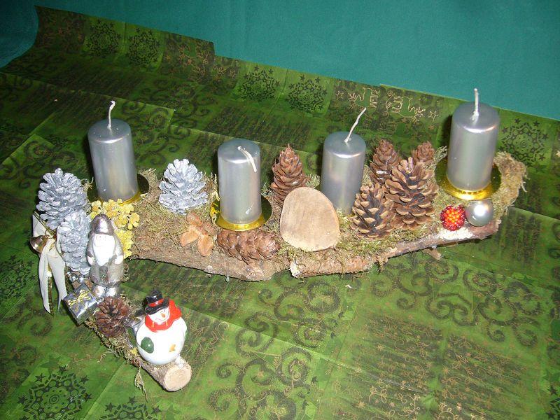 Etwa 50 cm langes und teils 25 cm tiefes Astgesteck mit natürlichen und silbernen Kiefernzapfen und ebenfalls 4 silbernen Stumpenkerzen mit Weinhnachts- und Schneemann zu 5,00 €.