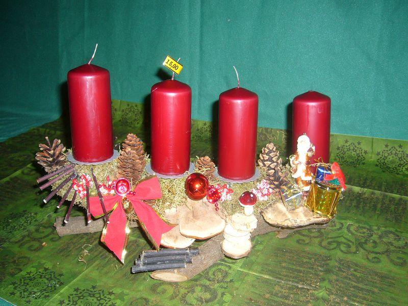 Gut 40 cm langes und 15 cm tiefes Astgesteck mit 4 dunkelroten Stumpenkerzen, Porlingen und Weihnachtsdekoration zu 15,00 €.