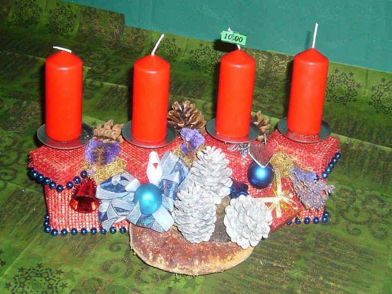Gut 30 cm langes und 20 cm tiefes 4er Gesteck mit roten Stumpenkerzen mit rotem Gitternetz, Rotrandigem Baumschwamm, Silberzapfen und Weihnachtsdekoration zu 10,00 €.