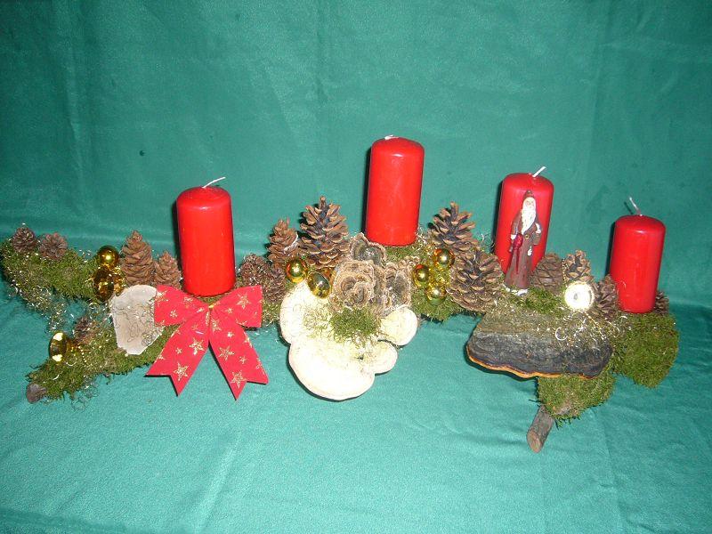Etwa 1 m langes, bis 25 cm tiefes 4er Gesteck mit roten Stumpenkerzen auf Ast mit Moos, Buckel - Tramete und Rotrandigem Baumschwamm, Kiefernzapfen und Weihnachtsdekoration zu 20,00 €.
