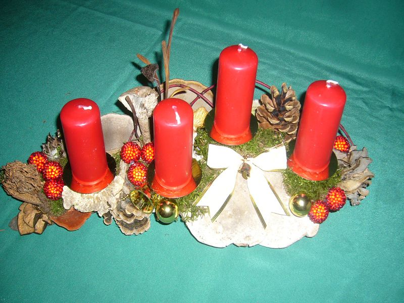 Etwa 40 cm langes und 20 cm tiefes 4er Gesteck mit roten Stumpenkerzen, vielen verschiedenen Pilzen, Moos und Weihnachtsdekoration zu 12,50 € - Verkauft.