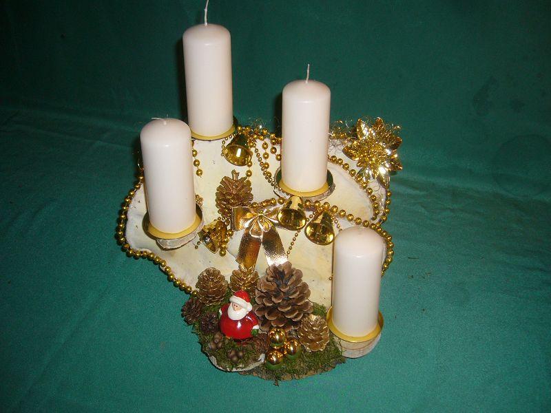 Weißgoldenes 4er Gesteck mit weißen Stumpenkerzen auf Holzscheibe mit großem, doppeltem Rotrandigem Baumschwamm mit Moos, Zapfen und goldener Weihnachtsdekoration zu 20,00 €.