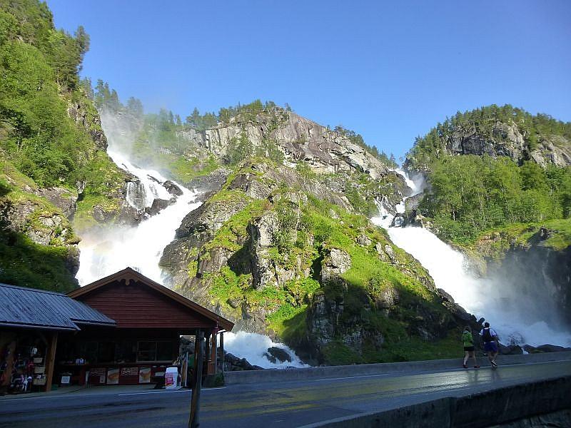 Unzählige Wasserfälle stürzen zu Tal, so auch dieser besonders spektakuläre Doppelfall, eine Touristenatraktion an derem Rand sogar eine Imbiss- und Souvenierbude aufgebaut wurde. Die Gischt spritzt bis auf die Fahrbahn.