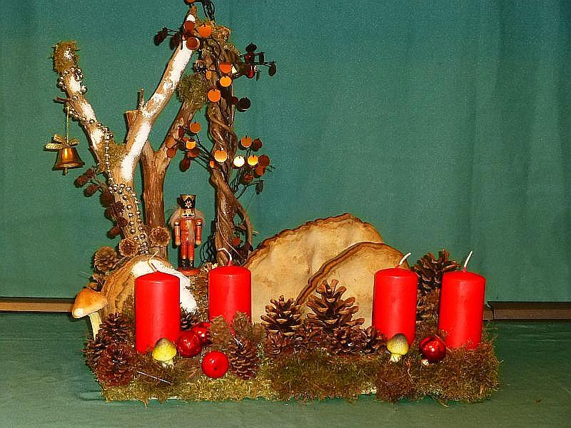 Rechteckiges, gut 40 cm langes und 20 cm tiefes 4er Gesteck mit roten Stumpenkerzen auf Holzplatte, mit dekorierten Zweigen, Echtem Zunderschwamm und Rotrandigem Baumschwamm. Mit Moos, Kiefernzapfen, künstlichen Pilzen, Nussknacker und Weihnachtsdekoration zu 20,00 €.