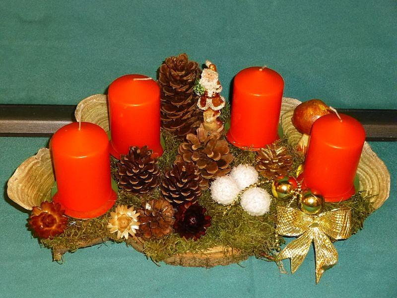 Halbrundes 4er Gesteck mit orange Stumpenkerzen auf Holzscheibe. Etwa 35 cm lang und 20 cm tief. Dekoriert mit Striegeliger Tramete, Moos, Kiefernzapfen und Weihnachtsschmuck zu 12,50 €.
