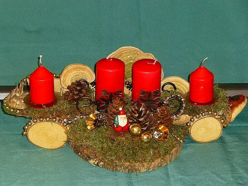 4er Gesteck mit roten Stumpenkerzen und Holzrädern mit Striegeliger Tramete und Rotrandigem Baumschwamm, Moos, Kiefernzapfen und Weihnachtsdekoration zu 10,00 €.