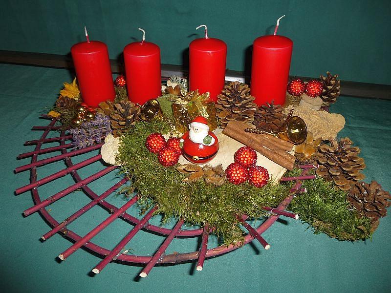 Rundes 4er Gesteck mit roten Stumpenkerzen, ca. 50 cm im Durchmesser mit Hartriegelgitter, Eichen - Wirrling, Birken - Blättling, Rotrandigem Baumschwamm, Moos, Kiefernzapfen und Weihnachtsdekoration zu 25,00 €.