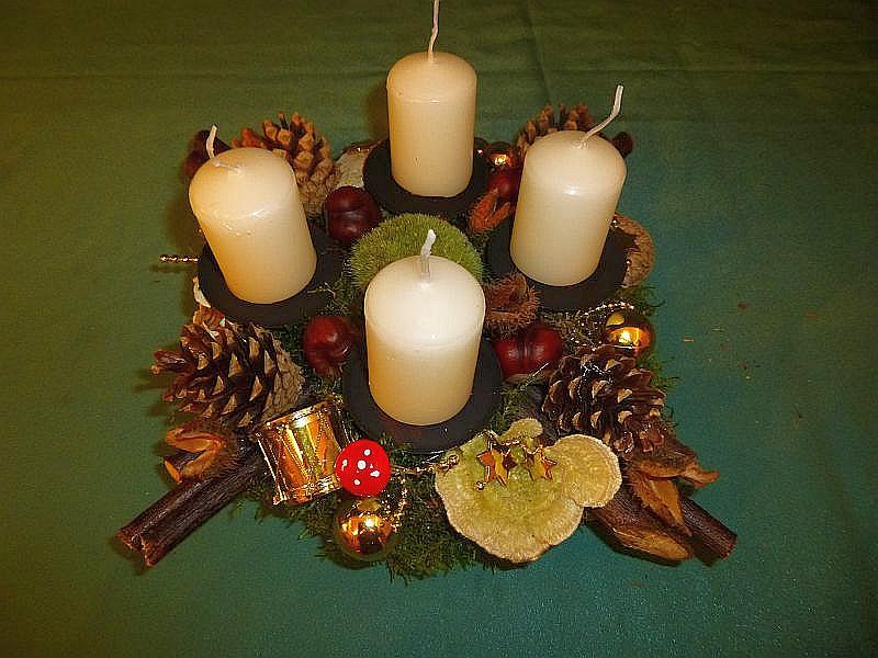 Rundliches Gesteck auf Baumscheibe, ca. 35 cm im Durchmesser mit weißen Stumpenkerzen, Striegeliger Tramete, Birken - Blättling, Kastanien und Kiefernzapfen sowie Weihnachtsdekoration zu 12,50.