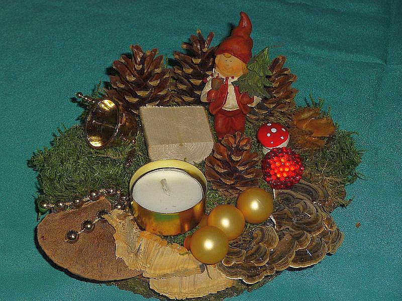 Rundliches Gesteck mit Teelicht auf Holzscheibe mit Rötender Tramete, Eichen - Wirrling, Schmetterlings - Tramete, Moos, Kiefernzapfen, Holzstück und Weihnachtsdekoration zu 8,00 €.